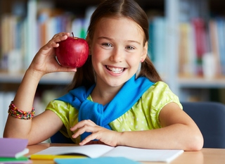 Portrait of happy schoolgirl with big red apple looking at camer